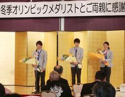 壇上であいさつする選手たち。左から平野歩夢、清水礼留飛、小野塚彩那の3選手=10日、新潟市中央区