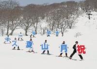 月山スキー場開きを祝うプラカードを持ってゲレンデを滑るスキーヤー=10日、山形県西川町