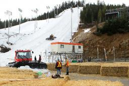 山肌が見えるモーグル、エアリアル会場(後方)。コース上に山頂から雪上車で雪が集められ、かさ上げのための干し草が準備される=飯塚晋一撮影