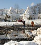 岩手雪まつりの会場で、地面が見えるほど雪不足の中、運んできた雪で雪像作りをする自衛隊員ら