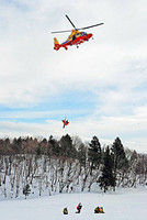 スキー事故を想定した救助訓練で、負傷者役を防災ヘリに引き上げる参加者たち(高島市・朽木スキー場)