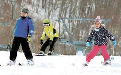 たっぷりと雪が残るゲレンデで滑りを楽しむ子どもたち=23日午後1時20分ごろ、スプリングバレー泉高原スキー場