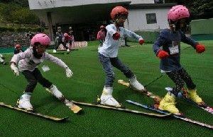 転ばないようにバランスを取りながら人工芝スキーを練習する坂梨小の児童