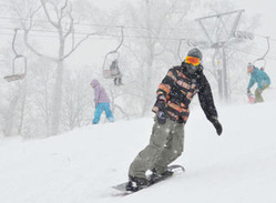 雪が降りしきる中、来場者はスキーやスノーボードを楽しんでいた=喜茂別町の中山峠スキー場