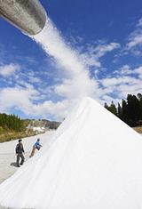 秋めく景色の中、ゲレンデに勢いよく噴射され、雪山をつくる人工雪=22日午前11時50分、郡上市白鳥町石徹白、ウイングヒルズ白鳥リゾート