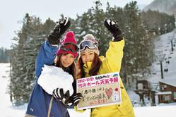 ゲレンデで天気予報のボードを掲げる一般女性=長野県白馬村で(白馬さのさか提供)