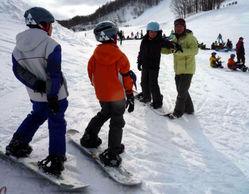 インストラクターの指導でスノーボードに挑戦する星置東小の児童たち=札幌市手稲区のスキー場で