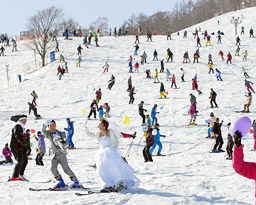祝福の風船が彩るゲレンデで、寄り添って滑る新郎と新婦=郡上市高鷲町、ダイナランド