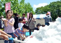 【写真=夏油高原スキー場から運ばれた雪で遊ぶ子どもたち=18日、東京都江東区】