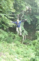 木の間に渡したワイヤロープを滑って実演する施設のスタッフ