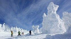 真っ青な空のもと、巨大な樹氷の脇をすり抜けるスキーヤーら=山形市蔵王温泉の蔵王温泉スキー場で