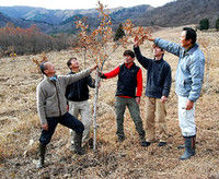ゲレンデ跡に植樹したクヌギの成長を見守る今森さん(左)と住民たち(昨年12月、高島市マキノ町・マキノスキー場)