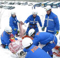 雪の中から、遭難者に見立てた人形を救助する機動隊員