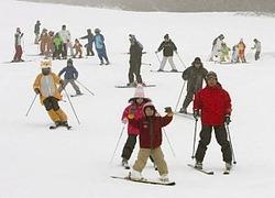 時折、雪が舞うゲレンデで初滑りを楽しむ人たち=18日午前9時32分、愛知県豊根村の茶臼山高原スキー場で