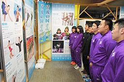 同世代の選手らの活躍を伝える写真を鑑賞する高校生=県庁