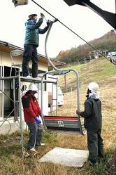 本格的な雪シーズンを前に次々とリフトの座席を取り付ける従業員(高山市で)