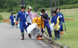 夏のゲレンデでごみを拾う妙高高原北小の児童=6日、妙高市の赤倉観光リゾートスキー場