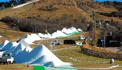 黒っぽい造雪機(右)からパイプで送られた人工雪が次々と白い山になっていく=九重町湯坪