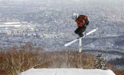 札幌の街並みに向かってジャンプし、技を決めるスキーヤー=札幌市手稲区のサッポロテイネ(岩崎勝撮影)