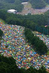 「フジロックフェスティバル'08」でスキー場のゲレンデに張られた色とりどりのテント。奥は野外ステージ=新潟県湯沢町の苗場スキー場で2008年7月25日午後2時4分、本社ヘリから長谷川直亮撮影
