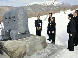 建立された慰霊碑の碑文を見る遺族ら(14日午前、江府町の奥大山スキー場で)