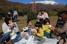 大山の紅葉と冠雪を背にバーガーを頬張る家族連れ=3日、江府町御机の奥大山スキー場