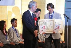 全日本スキー連盟のソチ五輪メダリスト顕彰式で、メダル2個分の賞状と目録を記念撮影用に持たされて笑みのこぼれるジャンプの葛西紀明(右)=山本晋撮影
