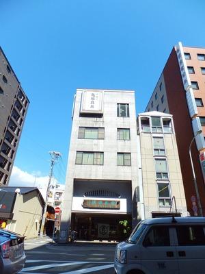 """四条通りを挟んで""""亀屋良長""""のビルを見る"""
