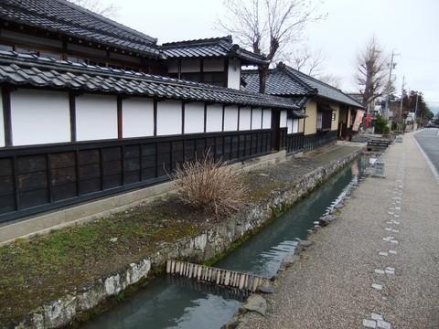 長屋門形式の黄色い門と塀沿いのカワ