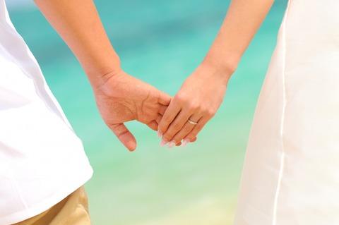 新郎新婦:海辺で手をつなぐ