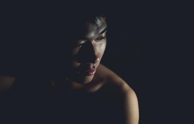暗い顔をした闇にいる男性