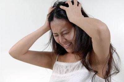 女性頭を抱える画像