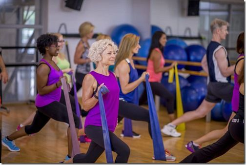 A multi-ethnic group of individuals are working out in a fitness class by using resistance bands.