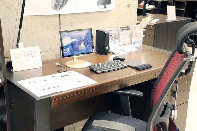 デスクにパソコンやプリンターなどが置かれている。