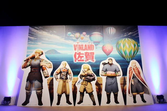 書き下ろしイラストには、日本のヴィンランド佐賀県の麦畑、玄界灘、熱気球が描かれている ©幸村誠・講談社/ヴィンランド・サガ製作委員会