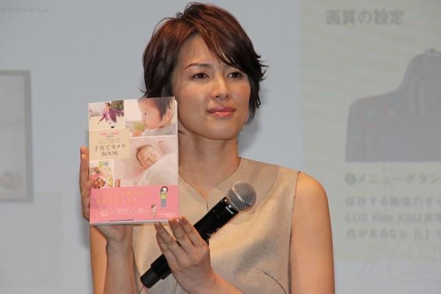 「子育てカメラBOOK」を手に持つ、吉瀬美智子さん