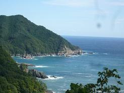 山あいの道の 合間に岸壁と海