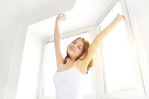 woman-waking-up-stretching-window