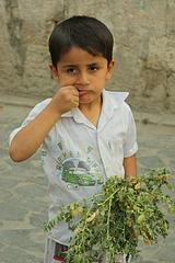 生のひよこ豆をおやつ代わりにむしゃむしゃと食べる少年。