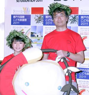 小豆島の特産品オリーブ製の冠、映画祭のTシャツを身に付けた大橋のぞみ(左)と金子修介監督。撮影:南 樹里