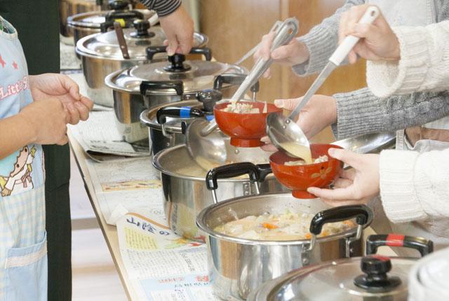 豚汁を母達が鍋からお椀に入れる作業