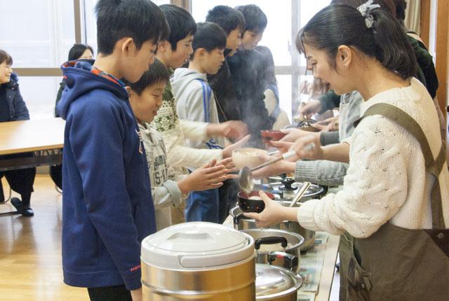 6年生の団員から豚汁をお椀に入れてもらいます
