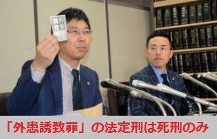 「外患誘致罪」と書かれた紙片をかざす佐々木弁護士