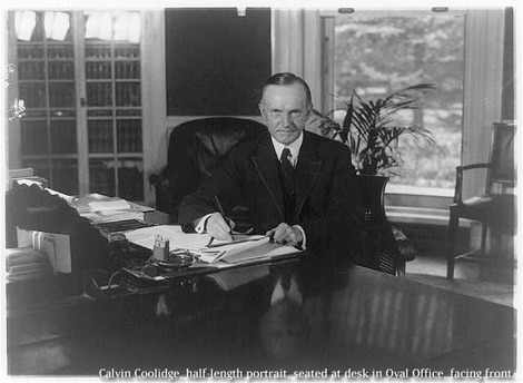 Calvin_Coolidge_seated_at_d