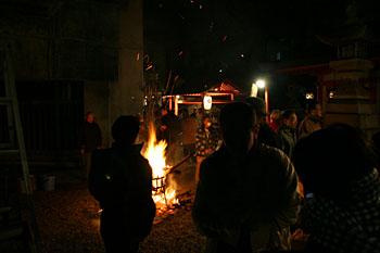 春日神社。境内ではかがり火が焚かれている。