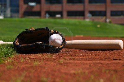3950768-baseball-glove-and-bat-on-a-ball-field