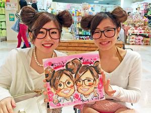 双子ルックで似顔絵を書いてもらっている女の子二人組