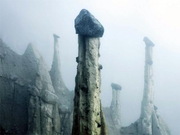 霧の中にそそり立つ幻想的な柱「地のピラミッド」が立ち並ぶアルプスの幻想的風景