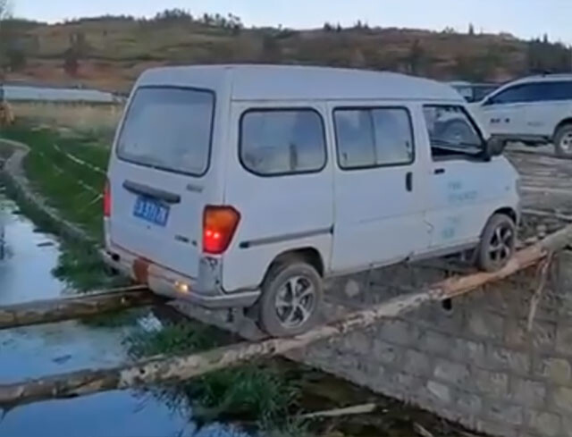 正気の沙汰かよ!細い丸太2本を川にかけ、バックで渡る車