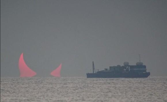 海面から突き出た巨大な赤い角。「悪魔の角」と呼ばれる気象現象が確認される(カタール)